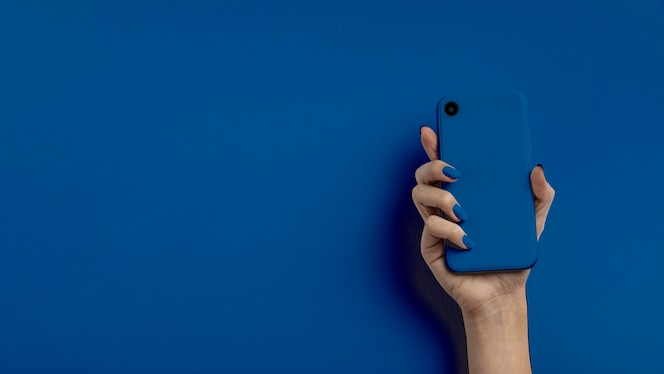 색상 배경에 휴대 전화를 들고 여성 손