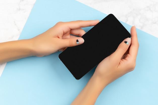 大理石と青の背景に携帯電話を持っている女性の手