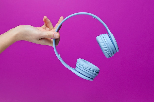 Female hand holding modern wireless blue headphones on a pink background.