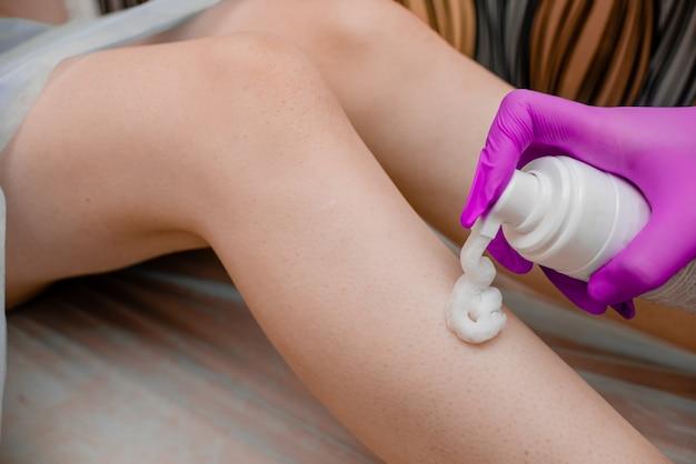 Female hand holding a moisturizer  depilation and beauty concept  spa salon.