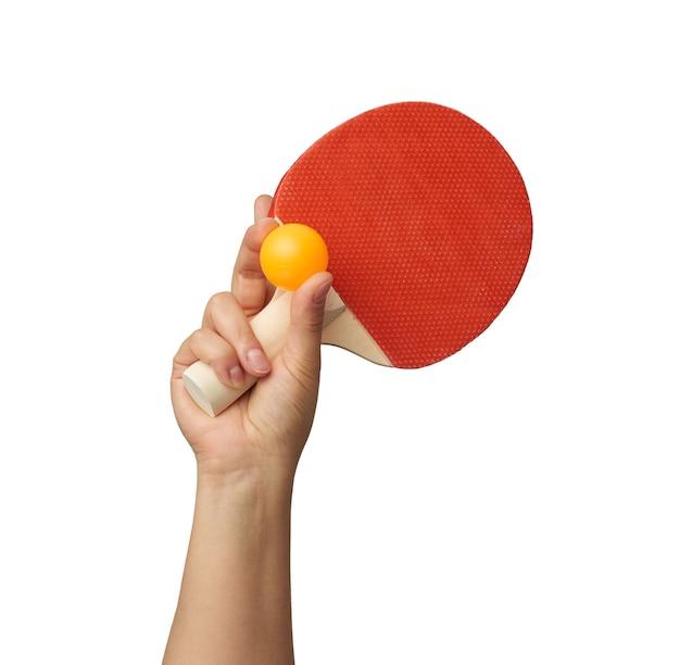 Женская рука держит оранжевый пластиковый мяч и деревянную ракетку для пинг-понга