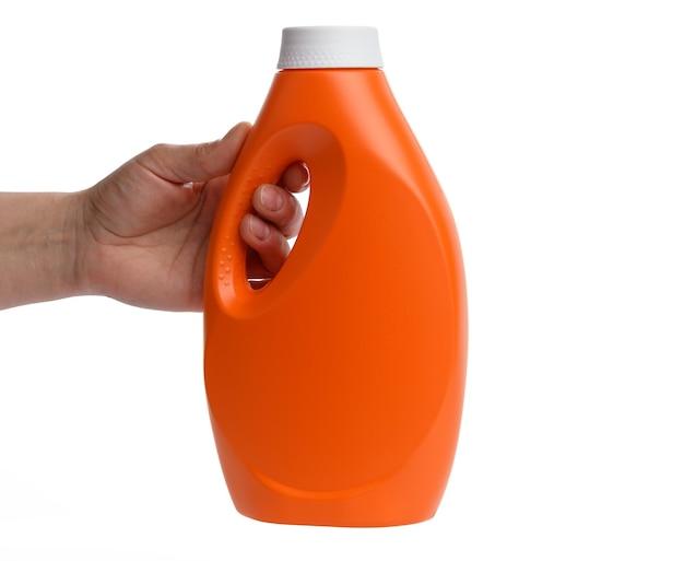 白い背景で隔離の液体洗濯洗剤のオレンジ色のプラスチックボトルを持っている女性の手