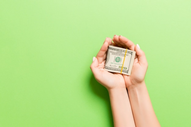 Female hand holding a pack of dollar bills