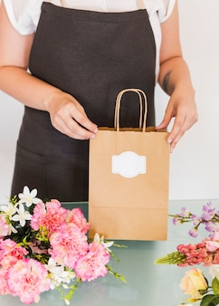 Female hand holding paper bag with bunch of flowers on desk