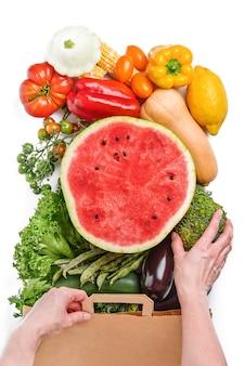흰색 바탕에 신선한 야채와 과일이 든 종이 가방을 들고 있는 여성의 손, 위쪽 전망. 텍스트를 위한 공간입니다.
