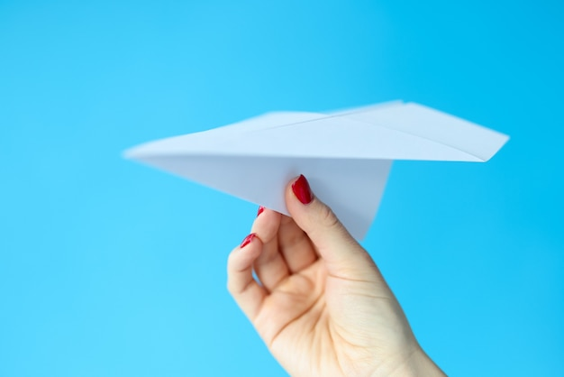 Female hand holding paper plane on blue background