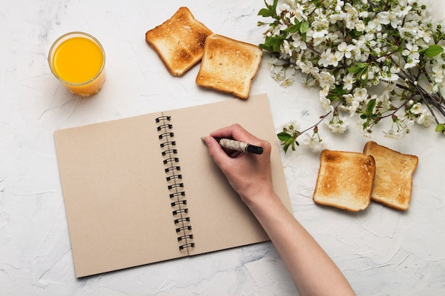 Female hand holding a pen, notepad, glass of orange juice, toast, spring branches tree with flowers. breakfast concept. flat lay, top view