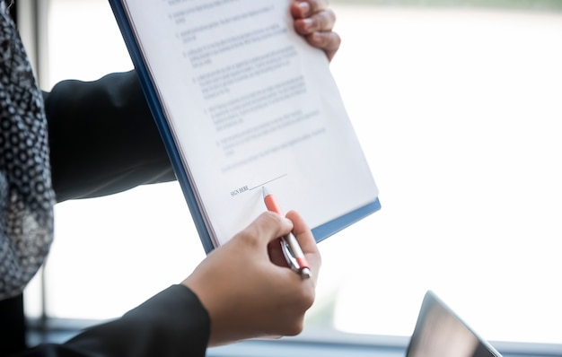 Female hand holding pen pointing at document paper for sign contract