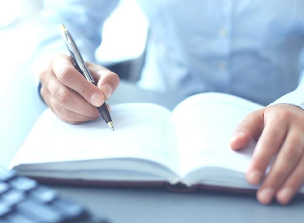 열린 노트북 시트에 메모할 준비가 된 펜을 들고 있는 여성의 손.
