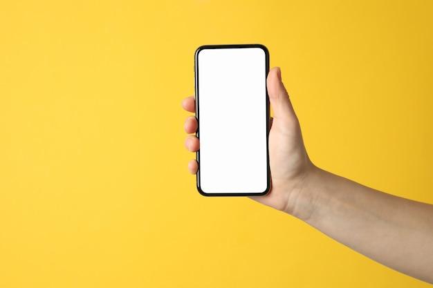 Женская рука держит телефон с пустым экраном на желтой поверхности