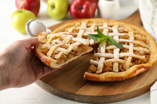アップルパイの部分を持っている女性の手。手作りの料理