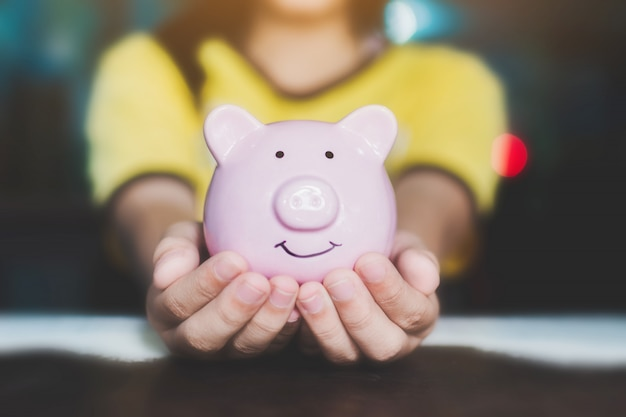 Female hand holding piggy bank