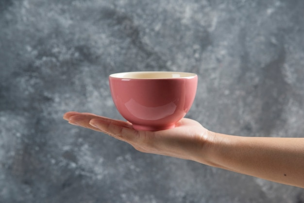 Female hand holding a pink bowl on gray.