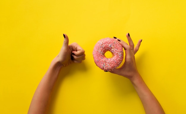 Female hand holding pink donut and showing like, ok sign over yellow background.