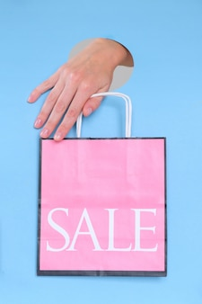 Female hand holding pink paper bag on blue