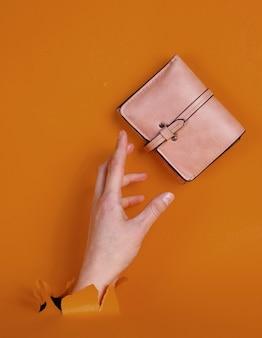 引き裂かれたオレンジ色の紙を通してピンクの財布を持っている女性の手。ミニマルなクリエイティブなファッションコンセプト