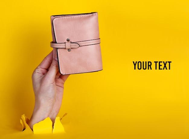 引き裂かれた黄色い紙を通してピンクの財布を持っている女性の手。ミニマルなクリエイティブなファッションコンセプト。コピースペース