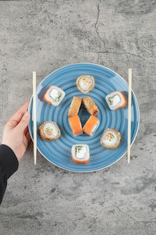 Female hand holding plate of delicious sushi rolls on marble background
