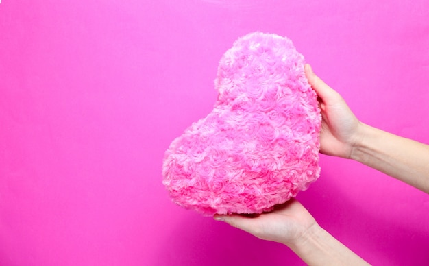 Female hand holding plush heart on a pink background.