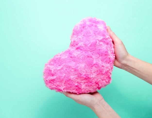 Female hand holding plush pink heart on blue background.