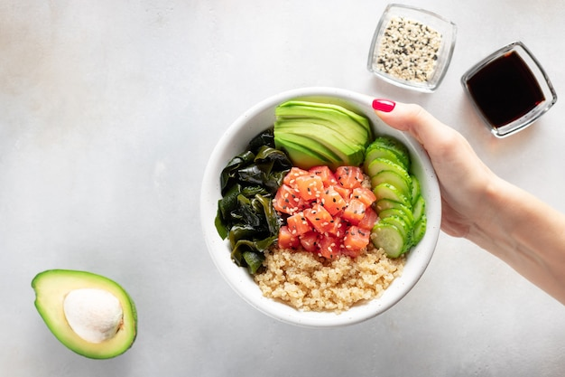 Female hand holding poke bowl with quinoa, salmon, avocado, wakame seaweed.