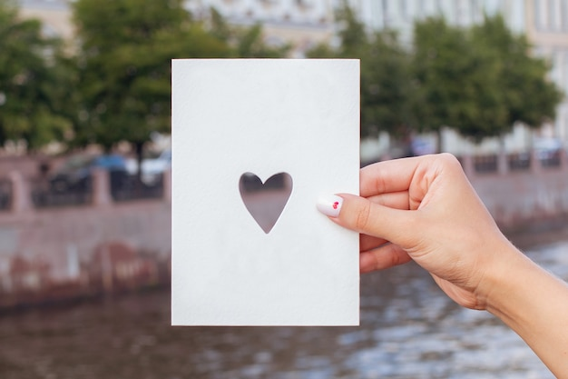 川の背景にコピースペースとはがきを持って女性の手
