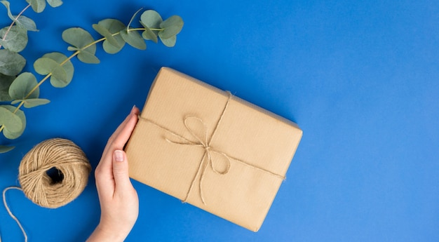 Female hand holding present box package and eucalyptus leaves on blue background. zero waste shopping concept. flat lay, top view, sustainable lifestyle.