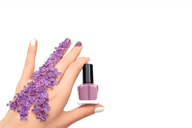 紫色のマニキュアボトルを持っている女性の手。春のコンセプトです。