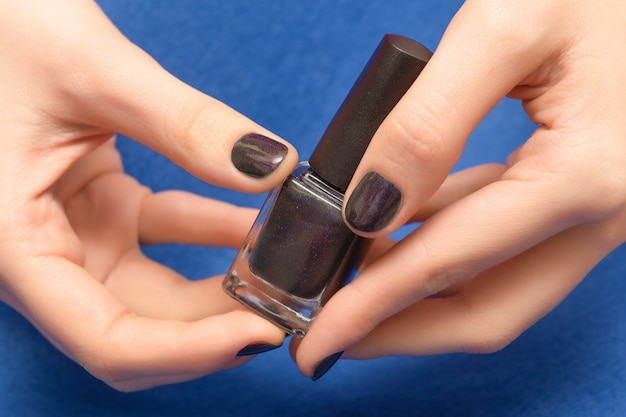 Женская рука держа фиолетовую бутылку лака для ногтей.