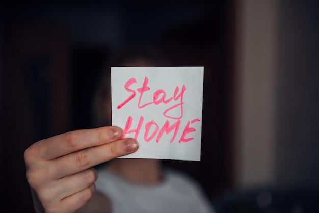 검역 메시지를 들고 여성 손 : 집에있어. 자기 격리 및 보호 개념. 텍스트 스티커