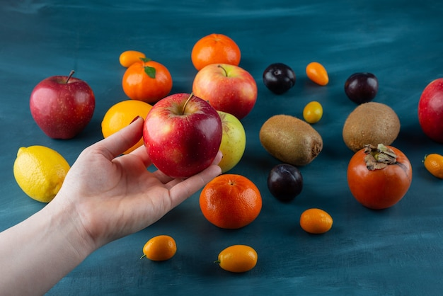 Female hand holding red apple on blue surface.