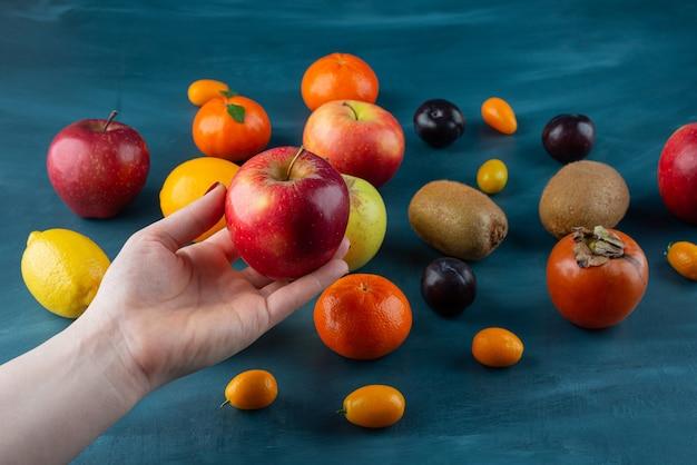 Женская рука держит красное яблоко на синей поверхности.