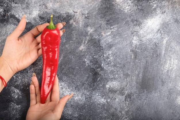 Женская рука, держащая красный перец чили на мраморной поверхности.