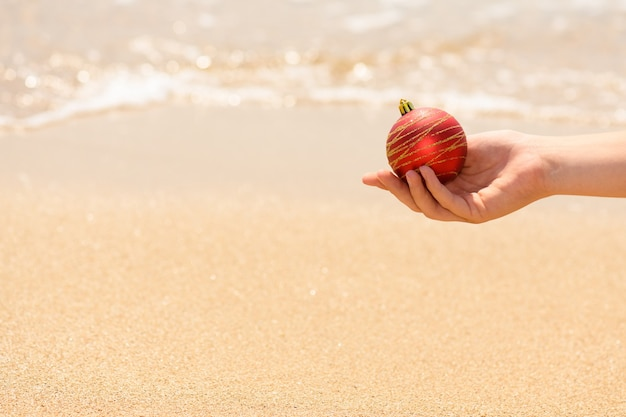 Female hand holding a red christmas ball on the sea background, christmas holidays on the beach