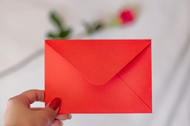 白い背景にコピー スペースを持つ赤い封筒を持っている女性の手
