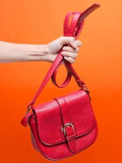Женская рука держит красную кожаную сумку за ремешок