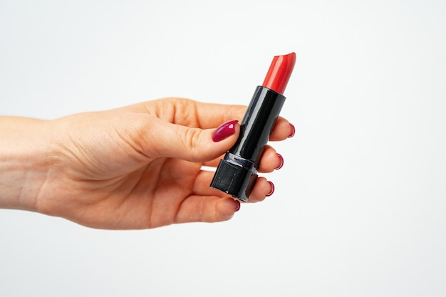 Female hand holding red lipstick against gray background close up