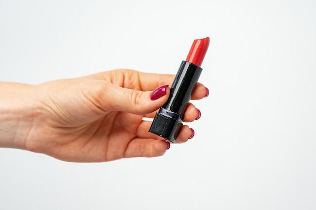 灰色の背景に赤い口紅を持っている女性の手