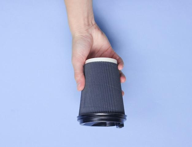 分離された赤い紙のコーヒーカップを持っている女性の手