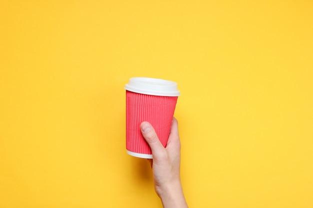 Женская рука держа красную бумажную кофейную чашку на желтой бумаге. вид сверху.