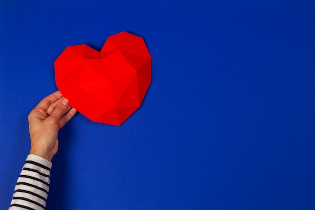 Female hand holding red polygonal heart on blue background. top view