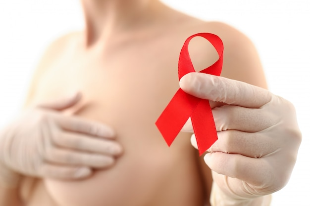 Female hand holding red ribbon cancer symbol breast closeup on doctor mammology