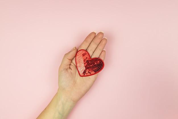 분홍색 배경에 빨간색 장식 조각이 마음을 잡고 여성 손.