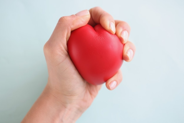 Female hand holding red toy heart on blue background closeup