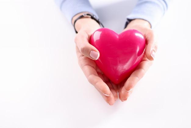 赤いおもちゃの心のクローズアップを持っている女性の手。臓器提供のコンセプト