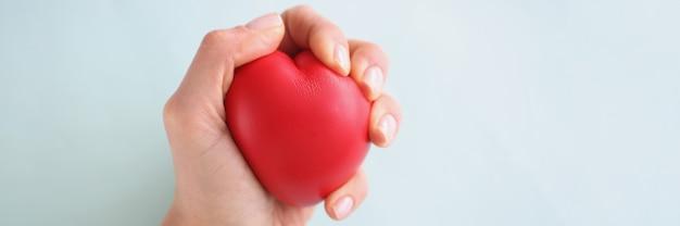 Женская рука держит красное игрушечное сердце на синем фоне крупным планом
