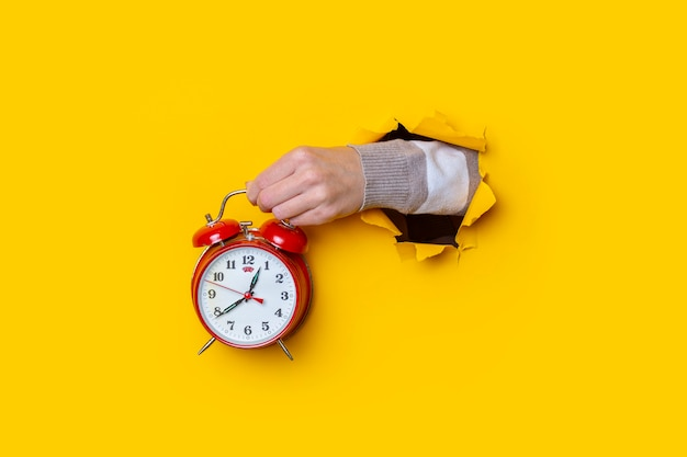 Female hand holding a red watch in a hole on a yellow background.