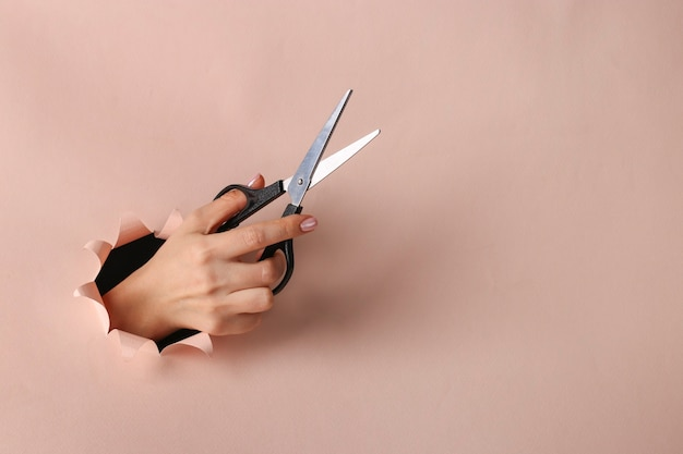 Female hand holding scissors through round hole in pink paper, copy space