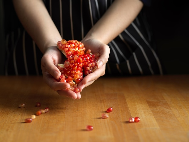 木製の台所のテーブルにザクロの種子を持っている女性の手
