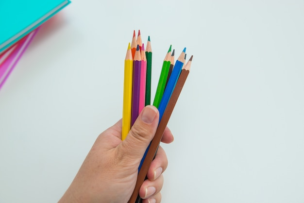 Female hand holding a set of colored pencils on light gray background with notebooks, copy space.